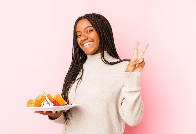 Jovem mulher afro-americana segurando um waffle isolado alegre e despreocupado, mostrando um símbolo de paz com os dedos.