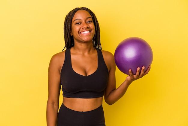 Jovem mulher afro-americana segurando uma bola de pilates isolada em fundo amarelo feliz, sorridente e alegre.