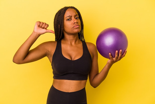 Jovem mulher afro-americana segurando uma bola de pilates isolada em fundo amarelo se sente orgulhosa e autoconfiante, exemplo a seguir.