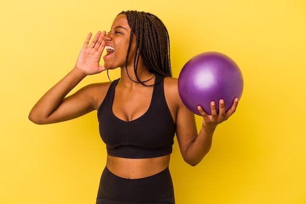 Jovem mulher afro-americana segurando uma bola de pilates isolada em um fundo amarelo gritando e segurando a palma da mão perto da boca aberta.