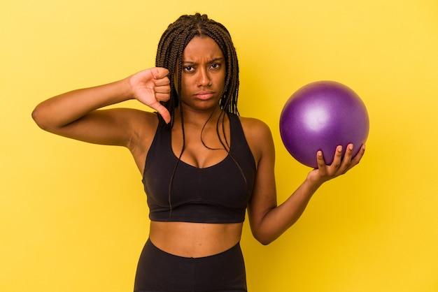 Jovem mulher afro-americana segurando uma bola de pilates isolada em um fundo amarelo, mostrando um gesto de antipatia, polegares para baixo. conceito de desacordo.