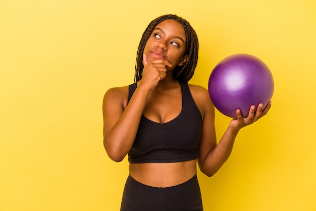 Jovem mulher afro-americana segurando uma bola de pilates isolada em um fundo amarelo, olhando de soslaio com expressão duvidosa e cética.