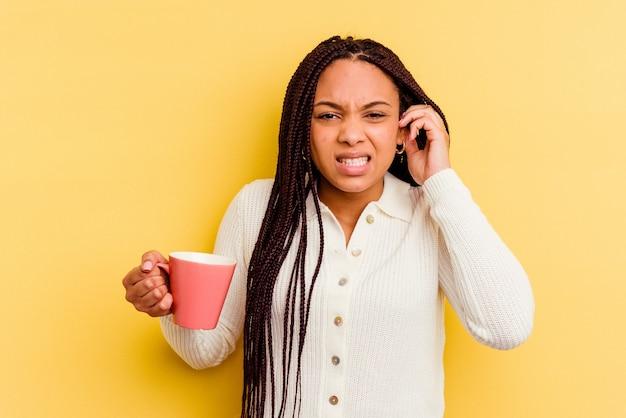 Jovem mulher afro-americana segurando uma caneca isolada, cobrindo as orelhas com as mãos.