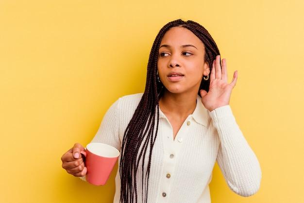 Jovem mulher afro-americana segurando uma caneca isolada, tentando ouvir uma fofoca.