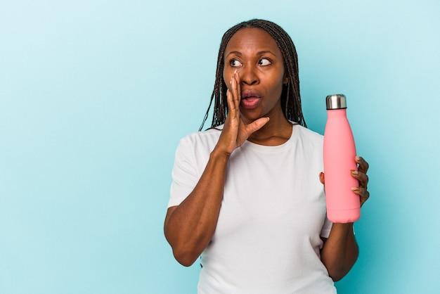 Jovem mulher afro-americana segurando uma cantina isolada em um fundo azul está contando uma notícia secreta de travagem e olhando para o lado