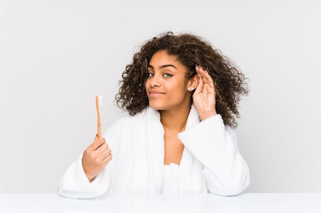 Jovem mulher afro-americana segurando uma escova de dentes, tentando ouvir uma fofoca.