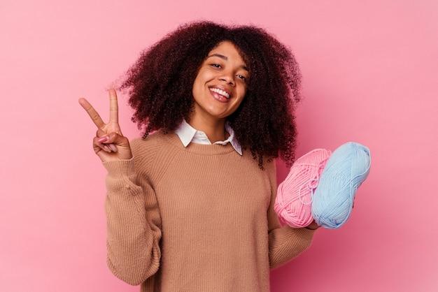 Jovem mulher afro-americana segurando uma linha de costura isolada no fundo rosa, mostrando o número dois com os dedos.