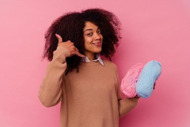 Jovem mulher afro-americana segurando uma linha de costura isolada no fundo rosa, mostrando um gesto de chamada de telefone móvel com os dedos.