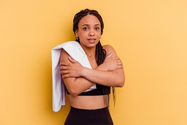 Jovem mulher afro-americana segurando uma toalha isolada na parede amarela, ficando fria devido à baixa temperatura ou uma doença