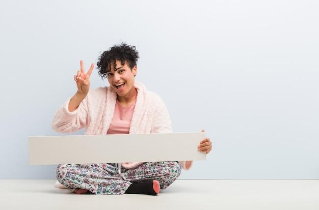 Jovem mulher afro-americana sentada com um cartaz mostrando sinal de vitória e sorrindo amplamente.