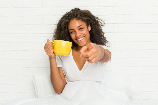 Jovem mulher afro-americana, sentada na cama segurando uma caneca de café, sorrisos alegres, apontando para a frente.