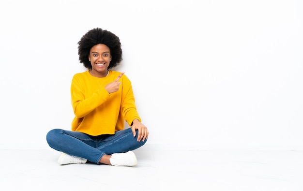 Jovem mulher afro-americana sentada no chão, apontando para o lado para apresentar um produto