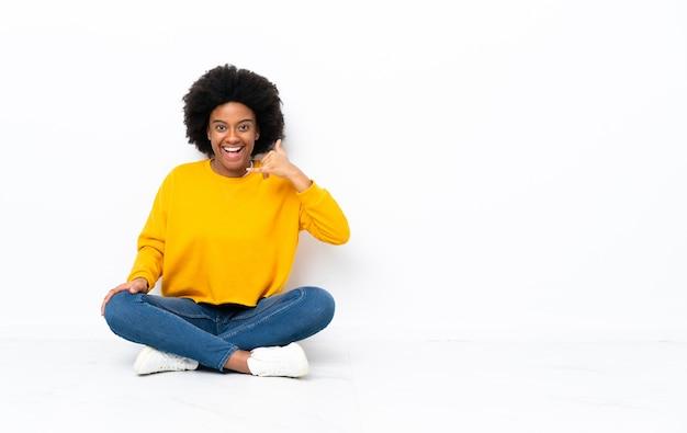 Jovem mulher afro-americana sentada no chão fazendo gesto de telefone. ligue-me de volta sinal