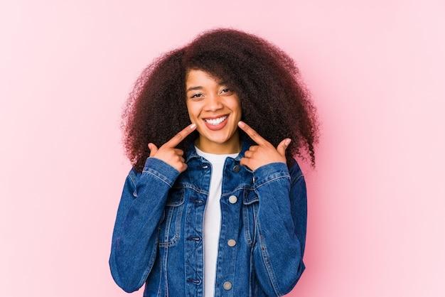 Jovem mulher afro-americana sorri, apontando os dedos na boca.