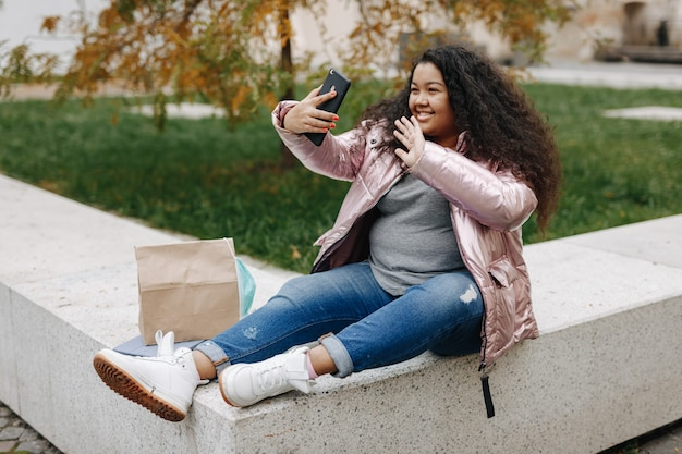 Jovem mulher afro-americana, sorrindo e gesticulando durante a videochamada no celular. muito feminina na máscara médica, tendo uma conversa online ao ar livre.