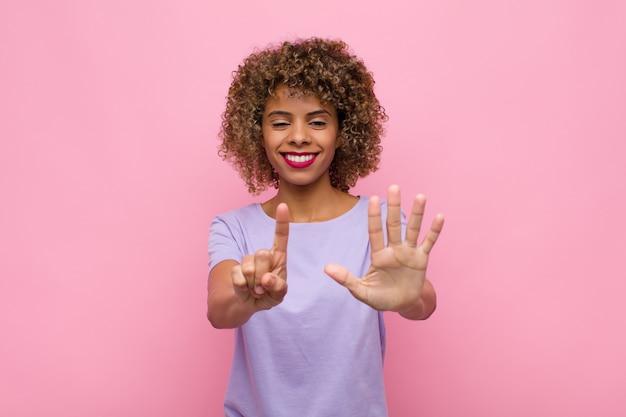 Jovem mulher afro-americana sorrindo e parecendo amigável, mostrando o número seis ou sexto com a mão para a frente, em contagem regressiva na parede rosa