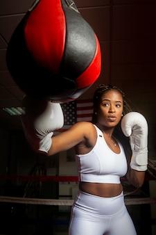 Jovem mulher afro-americana treinando boxe na academia com a bandeira dos estados unidos