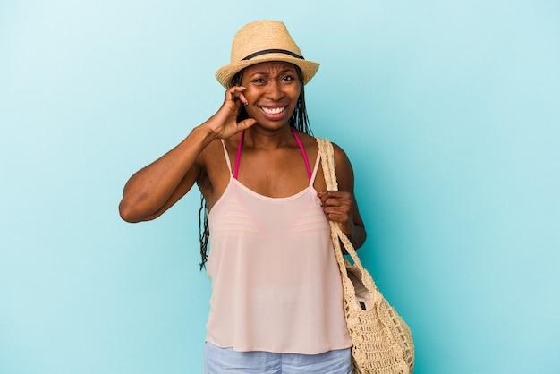 Jovem mulher afro-americana, vestindo roupas de verão, isoladas em fundo azul, cobrindo as orelhas com as mãos.