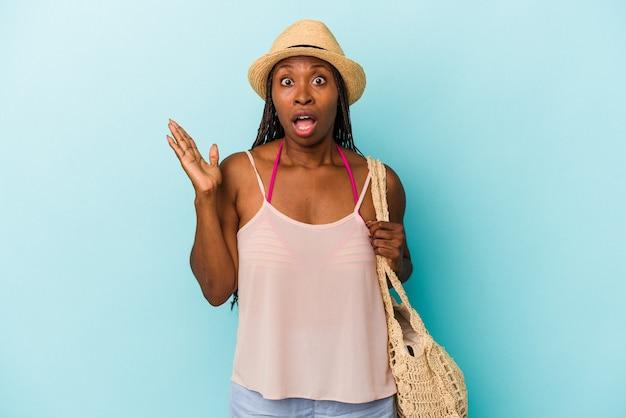 Jovem mulher afro-americana, vestindo roupas de verão, isoladas em fundo azul, surpresa e chocada.