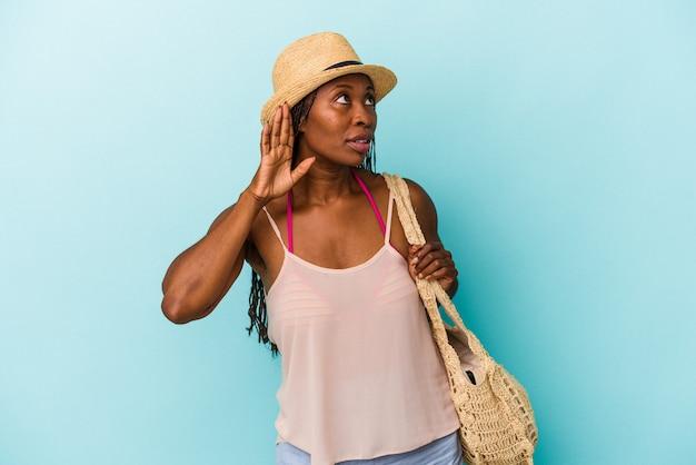 Jovem mulher afro-americana, vestindo roupas de verão, isoladas em um fundo azul, tentando ouvir uma fofoca.