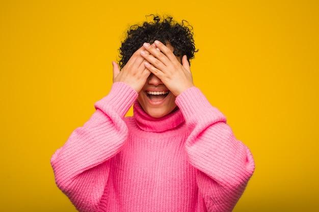 Jovem mulher afro-americana, vestindo um suéter rosa contras os olhos com as mãos, sorri amplamente esperando por uma surpresa.