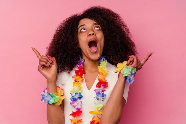 Jovem mulher afro-americana vestindo uma coisa havaiana apontando para cima com a boca aberta.