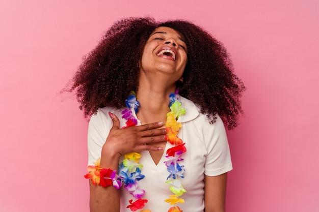 Jovem mulher afro-americana, vestindo uma roupa havaiana, ri alto, mantendo a mão no peito.
