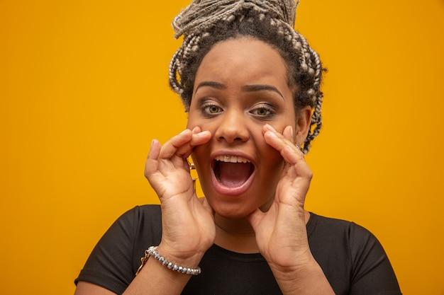 Jovem mulher afro-americano bonita sobre gritar amarelo isolado.