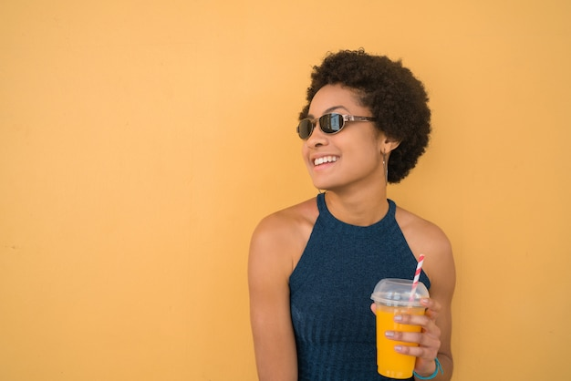 Jovem mulher afro bebendo suco de fruta fresca.