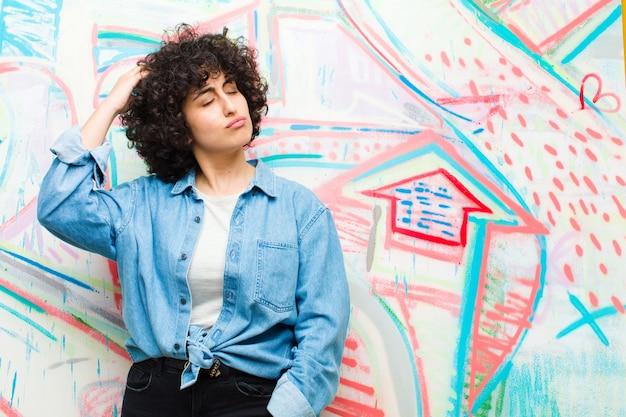 Jovem mulher afro bonita se sentindo confusa e confusa, coçando a cabeça e olhando para a parede lateral de grafite