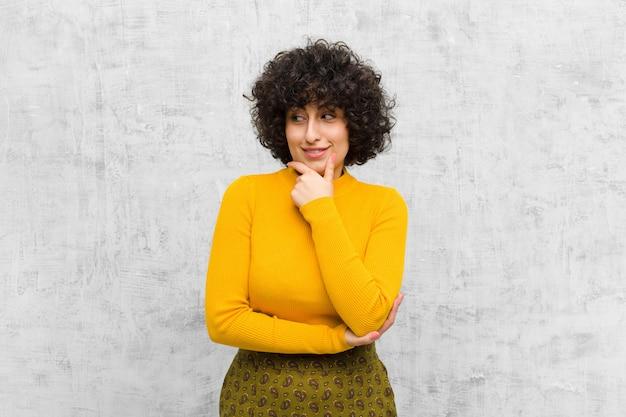 Jovem mulher afro bonita sorrindo com uma expressão feliz e confiante com a mão no queixo, pensando e olhando para o lado