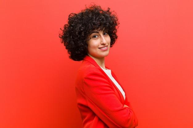 Jovem mulher afro bonita sorrindo para a câmera com os braços cruzados e uma expressão feliz, confiante e satisfeita, vista lateral