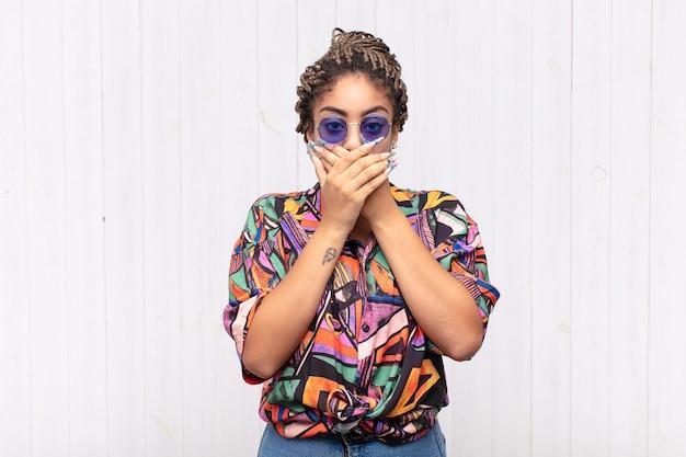 Jovem mulher afro cobrindo a boca com as mãos com uma expressão chocada e surpresa, mantendo um segredo ou dizendo oops