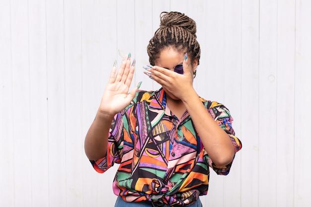 Jovem mulher afro cobrindo o rosto com a mão e colocando a outra mão na frente para parar a câmera, recusando fotos ou imagens