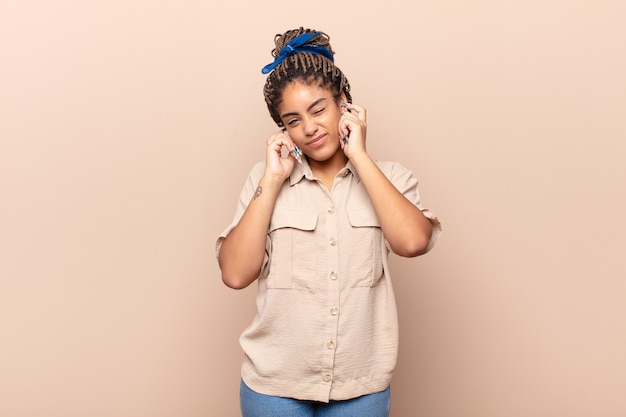 Jovem mulher afro com cara de zangada, estressada e irritada, cobrindo os ouvidos com um barulho, som ou música alta ensurdecedores