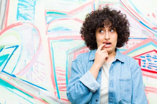 Jovem mulher afro com olhar surpreso, nervoso, preocupado ou assustado, olhando para o lado em direção ao espaço da cópia na parede de graffiti