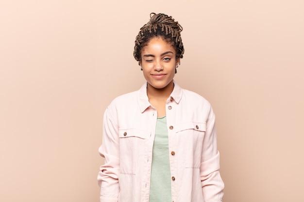Jovem mulher afro com uma aparência feliz e amigável, sorrindo e piscando os olhos para você com uma atitude positiva