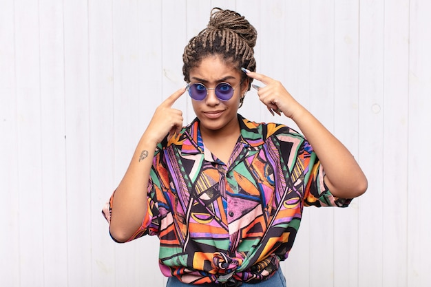 Jovem mulher afro com uma aparência séria e concentrada, fazendo um brainstorming e pensando sobre um problema desafiador