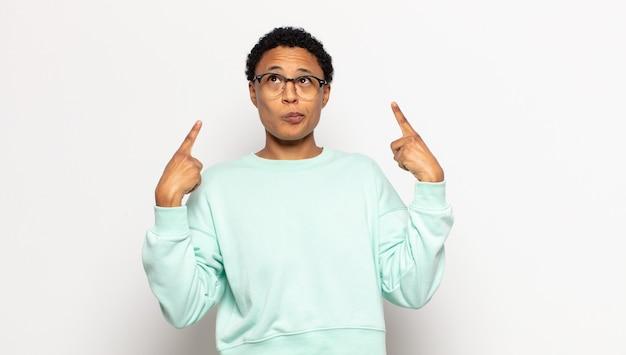 Jovem mulher afro com uma atitude ruim, parecendo orgulhosa e agressiva, apontando para cima ou fazendo sinal engraçado com as mãos