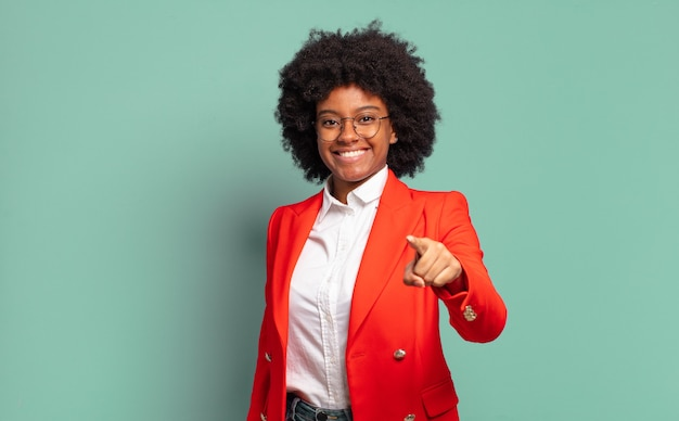 Jovem mulher afro contra parede isolada