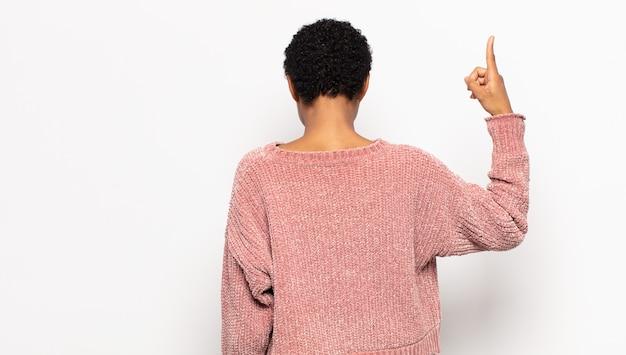 Jovem mulher afro em pé e apontando para um objeto no espaço da cópia, vista traseira