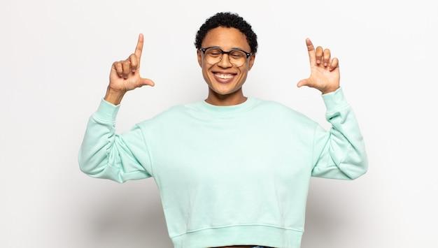Jovem mulher afro emoldurando ou delineando o próprio sorriso com as duas mãos, parecendo positiva e feliz, conceito de bem-estar