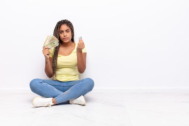 Jovem mulher afro fazendo capice ou gesto de dinheiro, mandando você pagar suas dívidas !. conceito de dinheiro