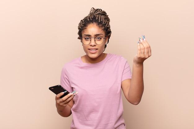 Jovem mulher afro fazendo capice ou gesto de dinheiro, mandando você pagar suas dívidas!
