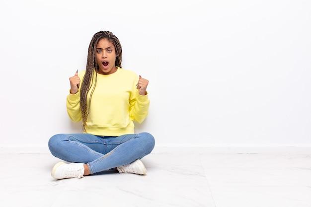 Jovem mulher afro gritando agressivamente com uma expressão de raiva ou com os punhos cerrados celebrando o sucesso