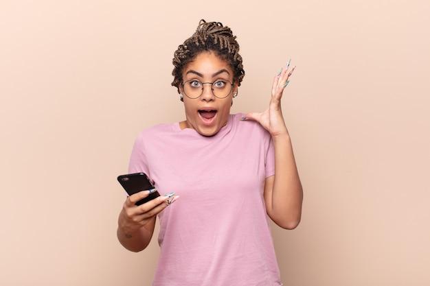 Jovem mulher afro gritando com as mãos no ar isolada