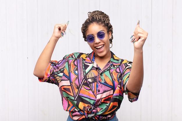 Jovem mulher afro gritando triunfantemente, parecendo uma vencedora animada, feliz e surpresa, comemorando