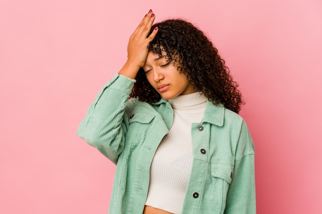 Jovem mulher afro isolada cansada e com muito sono mantendo a mão na cabeça