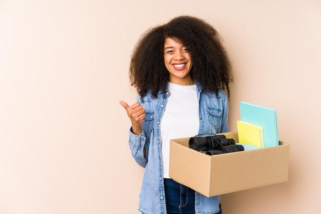 Jovem, mulher afro, movendo casa, isolado jovem, mulher afro, sorrindo, e, levantando polegar