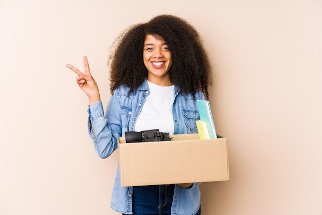 Jovem mulher afro, movendo-se para casa jovem mulher afro alegre e despreocupada, mostrando um símbolo de paz com os dedos.